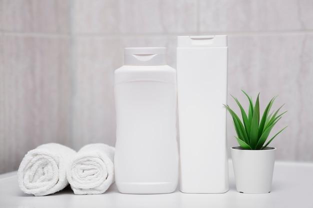 Frascos brancos de toalhas de xampu e uma planta verde natural em um pote cuidados com o corpo higiene e limpeza do corpo e pele cabelo limpo higienizado banheiro