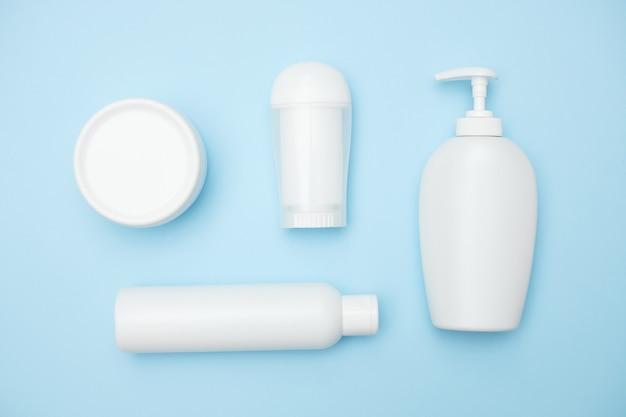 Frascos brancos do produto de higiene pessoal sobre um fundo azul, espaço da cópia, vista superior. foto de alta qualidade