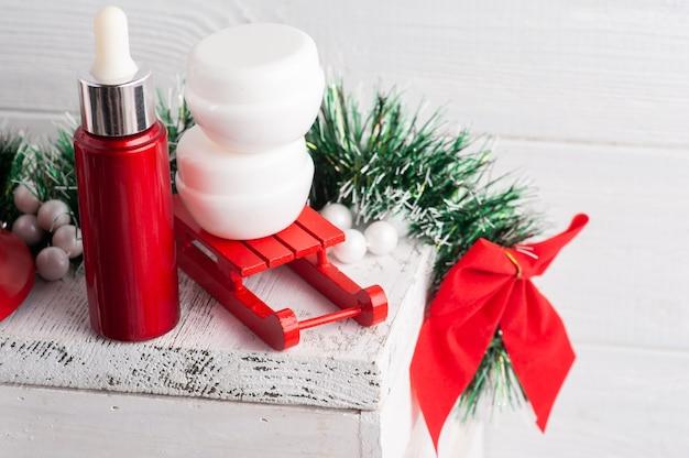 Frascos brancos na composição de natal vermelha com óleo essencial. zombe de produto de beleza