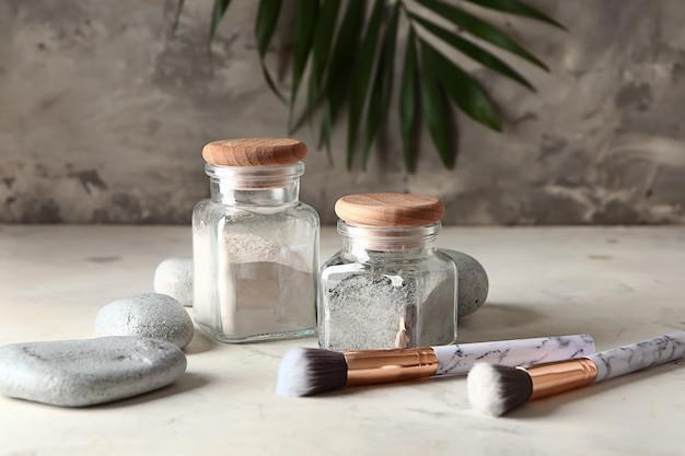 Frascos com argilas cosméticas, pedras e pincéis na mesa
