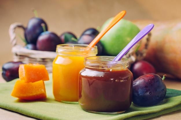 Frascos com comida para bebé e purê de abóbora com colher perto de frutas frescas