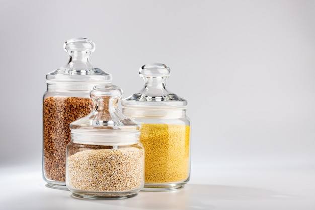 Frascos com cuscuz de trigo sarraceno e cevada em um fundo branco