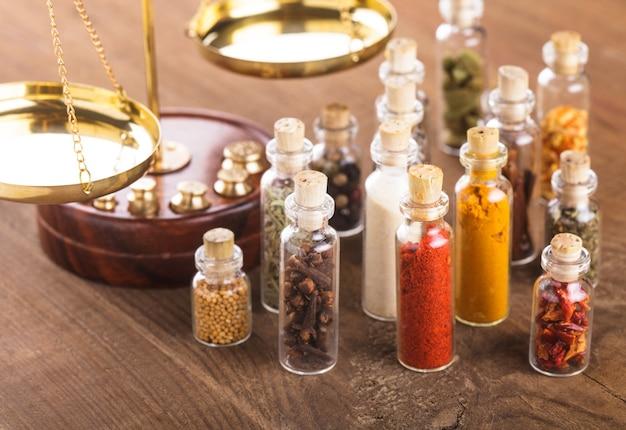 Frascos com especiarias e escalas na mesa, cozinha védica
