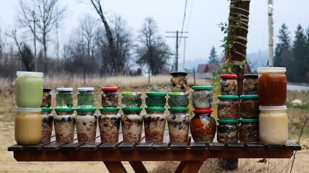 Frascos com nozes, frutas e mel natural na mesa de madeira da feira. venda de mel natural no mercado livre.