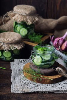Frascos com pepinos em conserva caseiros cortados em fatias com endro e alho na mesa de madeira rústica. colher vegetais para o inverno.