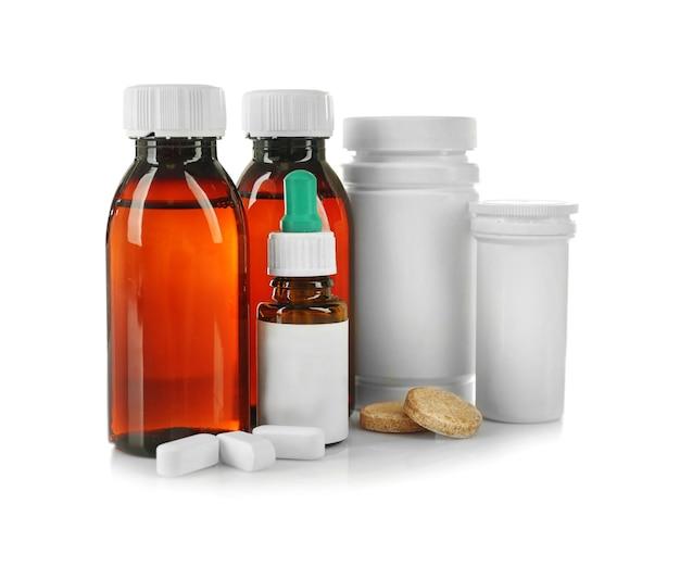 Frascos com xarope para tosse, pílulas e medicamentos isolados no branco