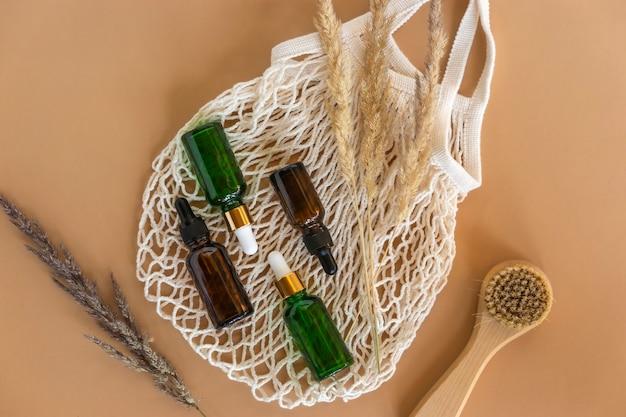 Frascos conta-gotas de óleo essencial natural ou soro, escova facial natural repousam em uma bolsa de rede