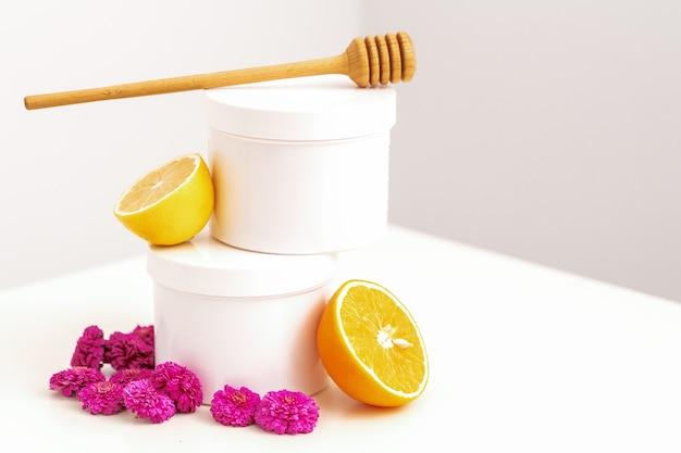 Frascos cosméticos brancos com um bastão de mel de madeira, limão fresco e flores de crisântemos.