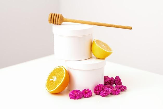 Frascos cosméticos brancos com uma vara de mel de madeira, limão fresco e flores de crisântemos em branco