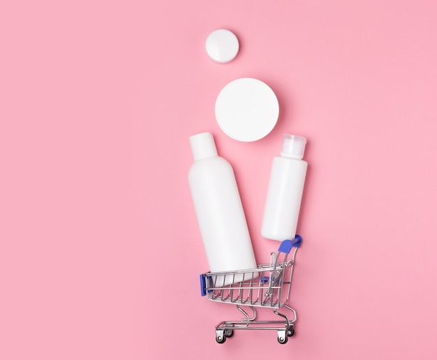 Frascos cosméticos brancos encontram-se em uma cesta de compras em um fundo rosa. compra em casa online. compra de produtos de desinfecção, lavanderia e cuidados.