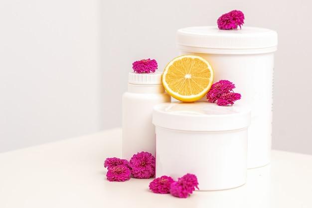 Frascos cosméticos brancos, recipientes, garrafa com flores frescas de limão e crisântemos.