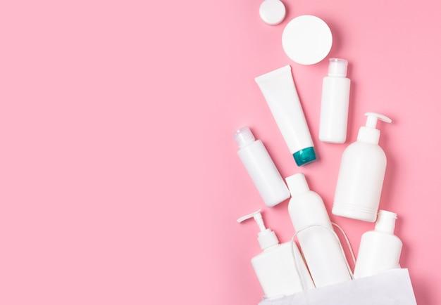 Frascos cosméticos brancos sobre um fundo rosa. cosméticos para cuidados com a pele