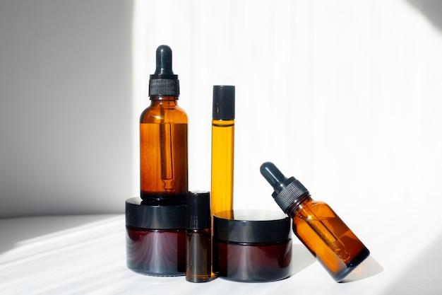 Frascos cosméticos com óleos em um fundo branco. luz e sombras. minimalismo. copie o espaço. cosmetology. cuidados com a pele. frascos de cosméticos. tratamento de spa