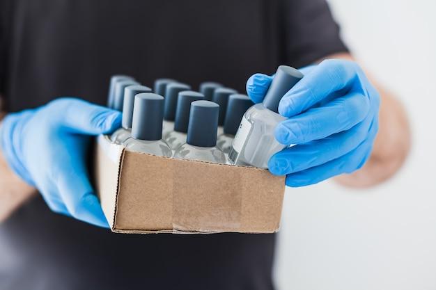 Frascos de álcool gel desinfetante higiênico para as mãos nas mãos de um homem
