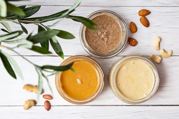Frascos de amêndoa, castanha de caju e manteiga de amendoim em uma mesa de madeira branca com um ramo de oliveira