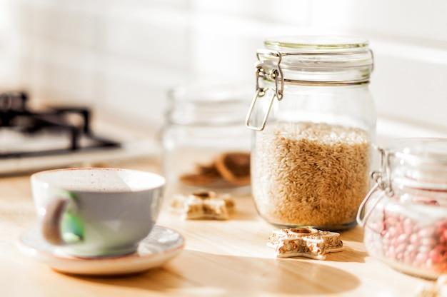 Frascos de arroz com feijão estão na cozinha. ao lado das latas há uma xícara de chá em um pires e biscoitos. foto horizontal