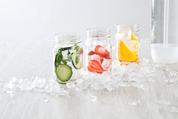 Frascos de closeup com gelo e vários recheios de laranja, morango, pepino e hortelã preparados para fazer limonada caseira fresca com água com gás