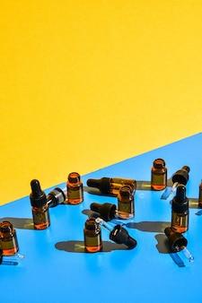 Frascos de conta-gotas com sombras escuras em fundo amarelo e azul. conceito moderno de minimalismo criativo. copie o espaço
