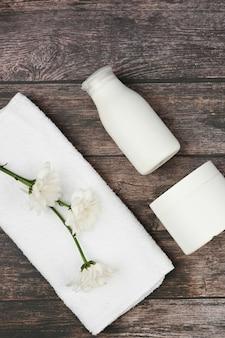 Frascos de cosméticos à base de plantas com uma toalha branca em cima. frascos de creme com ingredientes naturais.