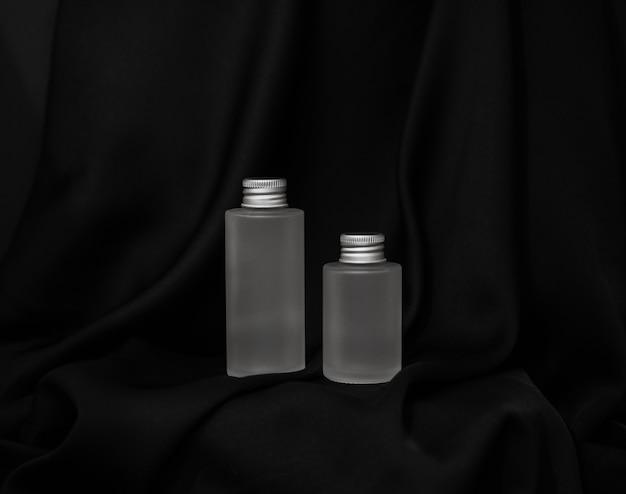 Frascos de cosméticos ã • wo ficam lado a lado em um fundo de seda preta