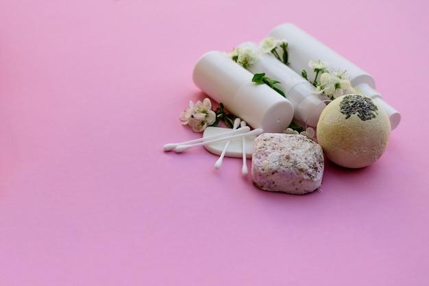 Frascos de cosméticos brancos, bomba de banho, sabonete artesanal, sal de banho, escova de massagem, esponja, cotonetes com flores de cerejeira em um fundo rosa. conceito de cosméticos orgânicos naturais.