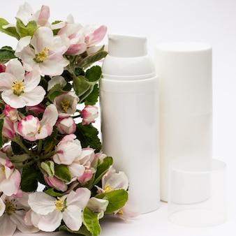 Frascos de cosméticos brancos com flores de pêra em um fundo branco. conceito de cosméticos orgânicos naturais.