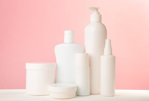 Frascos de cosméticos brancos na parede rosa. vista do topo