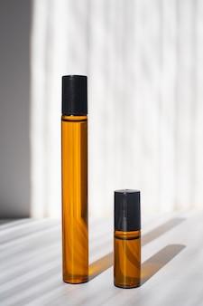 Frascos de cosméticos com óleos em um fundo branco luz e sombras minimalismo c