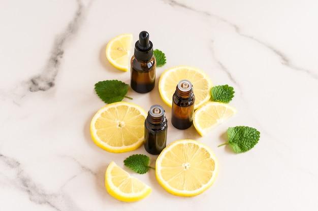 Frascos de cosméticos de vidro escuro com óleos essenciais de folhas de erva-cidreira e limão sobre uma mesa de mármore.