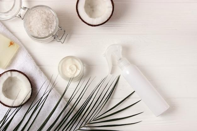 Frascos de cosméticos e coco na mesa, close-up e lugar para texto