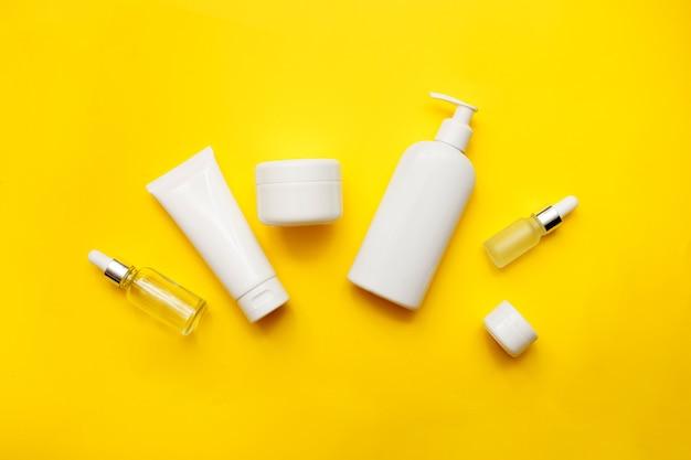 Frascos de cosméticos em fundo amarelo brilhante, vista superior, espaço de cópia. brincar. frascos brancos, acessórios de banho. conceito de cuidado de rosto e corpo.