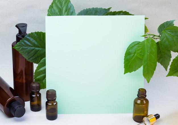 Frascos de cosméticos escuros e folhas naturais verdes sobre um fundo claro
