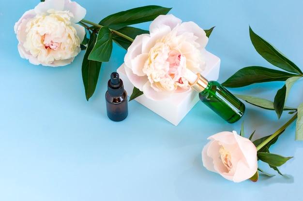 Frascos de cosméticos luxuosos com produtos para a pele anti-envelhecimento em fundo com flores de peônia, embalagem de rótulo em branco para design de marca de cuidado corporal.