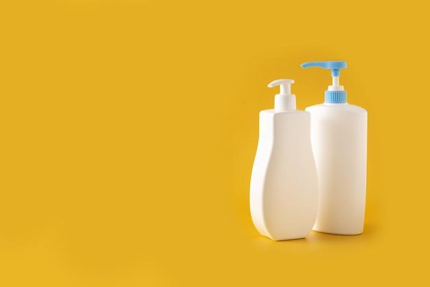 Frascos de cosméticos para bebês na superfície amarela
