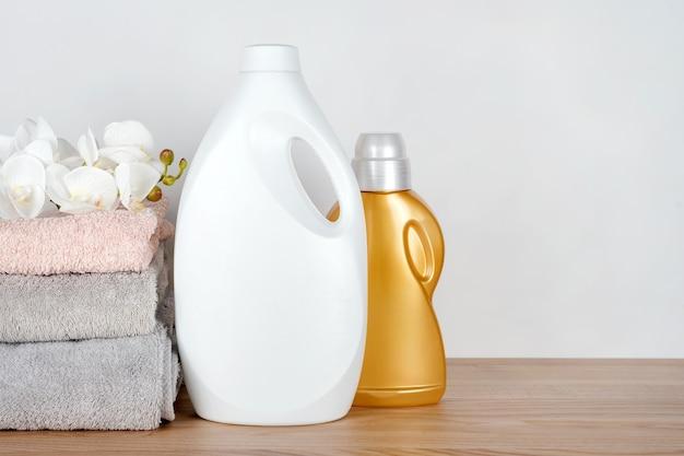 Frascos de detergente e amaciante com toalhas limpas e flores de orquídea na mesa de madeira. recipientes de produtos de limpeza. detergente líquido e condicionador. dia da lavanderia, conceito de limpeza.