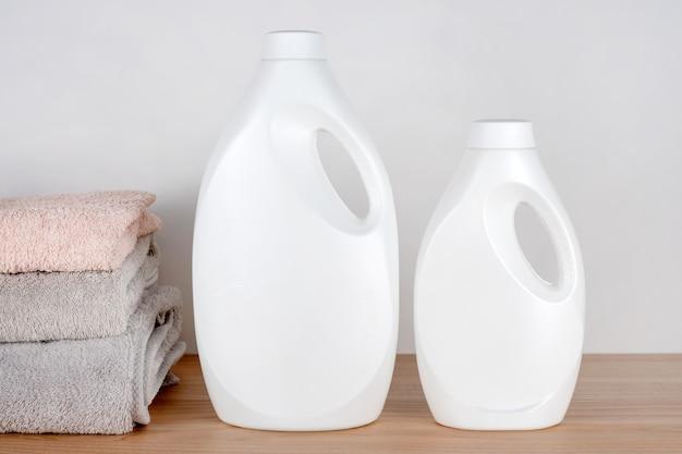 Frascos de detergente e amaciante com toalhas limpas na mesa de madeira. recipientes de produtos de limpeza. detergente líquido e condicionador. dia da lavanderia, conceito de limpeza.