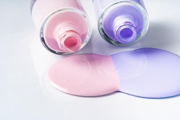 Frascos de esmalte derramado de cor pastel sobre branco