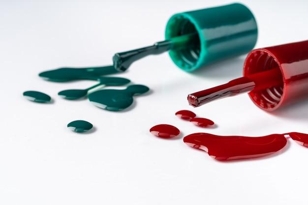Frascos de esmaltes coloridos brilhantes com gotas no fundo branco