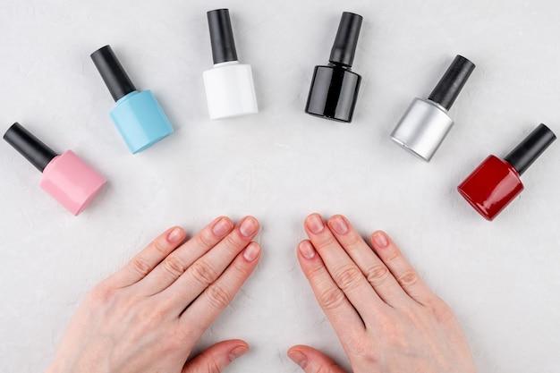 Frascos de esmaltes em cores diferentes e mãos com unhas curtas sem casaco no fundo branco