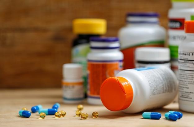 Frascos de medicina e comprimidos na mesa de madeira