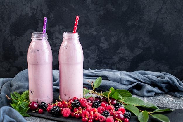 Frascos de milk-shake com cranberries, morangos e mirtilos