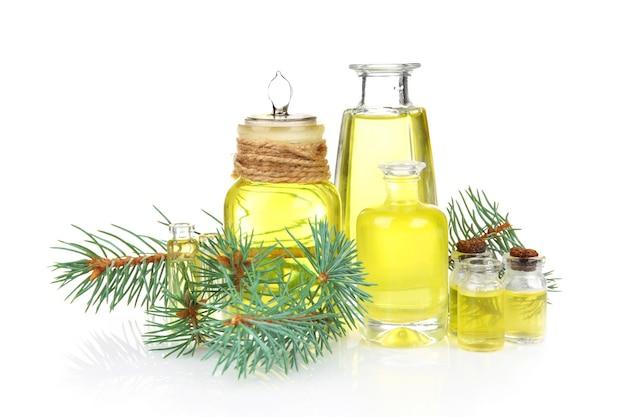 Frascos de óleo essencial de coníferas e ramo isolado no branco