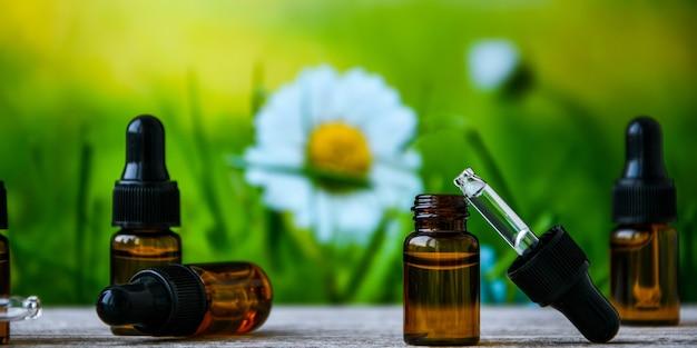 Frascos de óleo essencial e flores de camomila na mesa de madeira contra o fundo desfocado. espaço para texto. medicina alternativa à base de plantas.