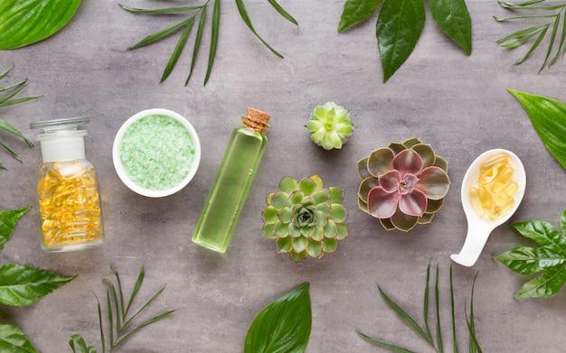 Frascos de óleo essencial, sal e plantas na mesa de madeira