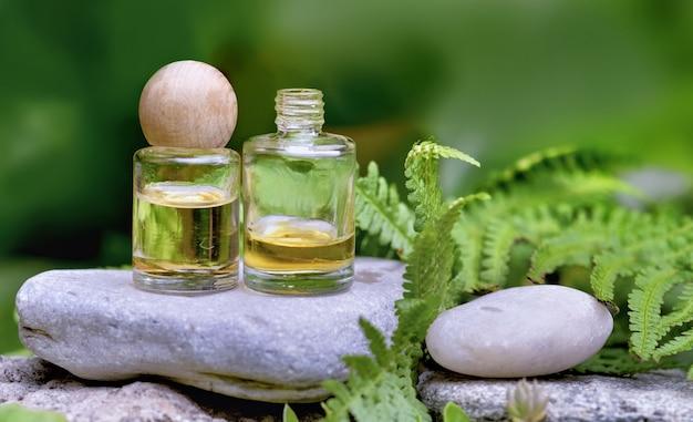 Frascos de óleos essenciais em uma pedra entre plantas verdes