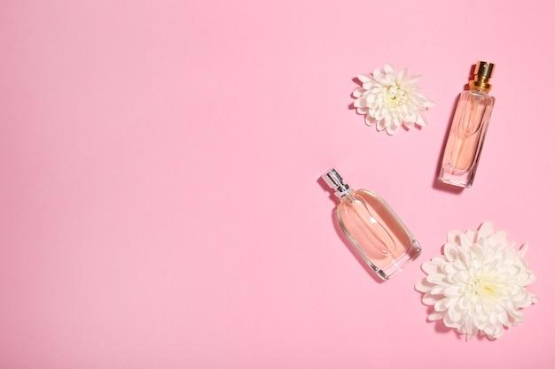 Frascos de perfume com flores em rosa