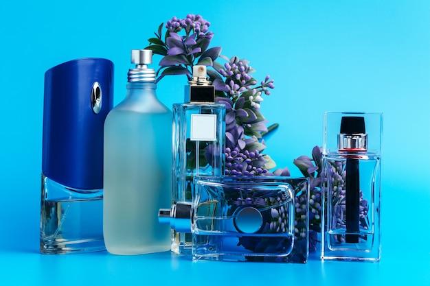 Frascos de perfume com flores em um azul claro