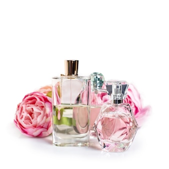 Frascos de perfume com flores na superfície clara