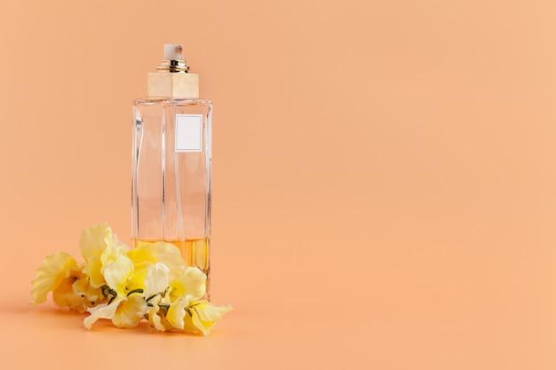 Frascos de perfume com pétalas de flores sobre fundo bege
