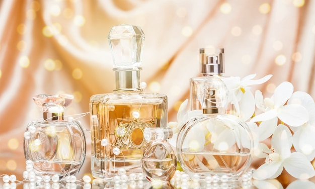 Frascos de perfume de vidro com flores e pérolas